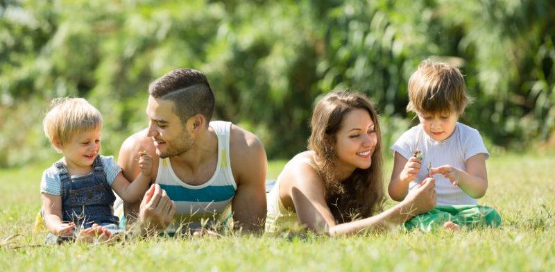 Rodzice z dziećmi bawiący się na trawie | fot. created by Bearfotos - Freepik.com